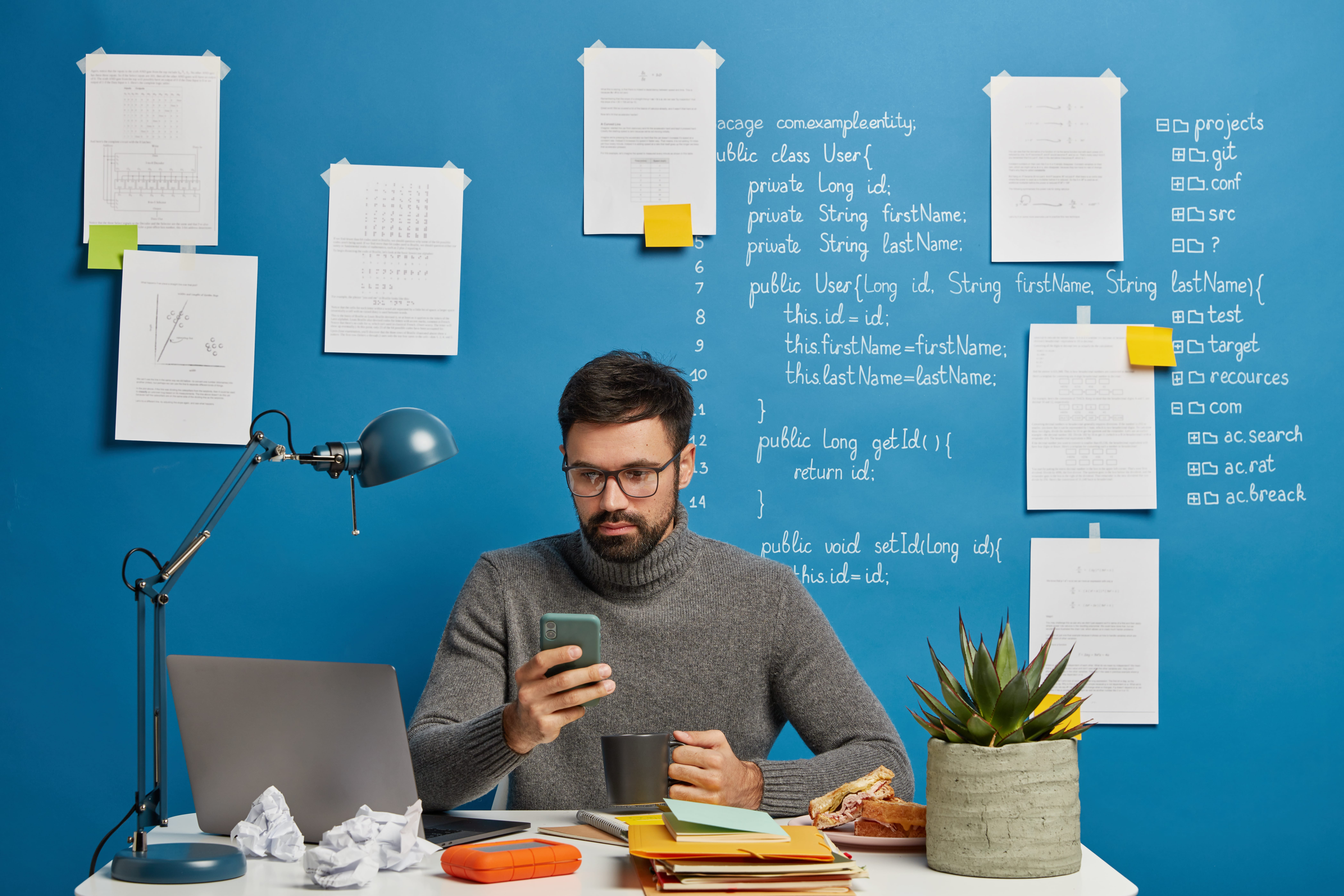 IT professional works on startup project, updates software and database on mobile phone, drinks hot beverage, sits at desktop against blue wall with written information. Computer hardware engineer